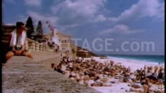 Vintage scene of man atop wall overlooking beach